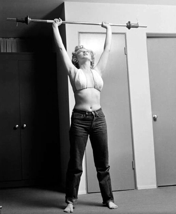 Marilyn Monroe shoulder pressing a barbell